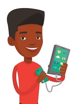 Mann, der smartphone von tragbarer batterie auflädt.