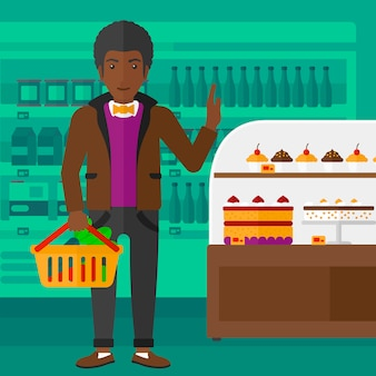 Mann, der supermarktkorb hält.