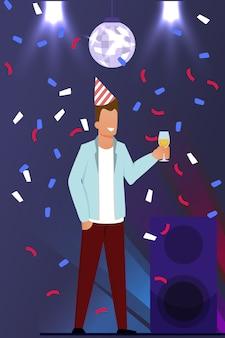 Mann, der unter konfetti-regen auf tanzfläche steht