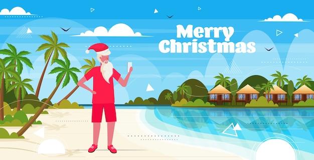 Mann, der weihnachtsmannhut mit smartphone am tropischen strand neujahrs-weihnachtsferienurlaub trägt