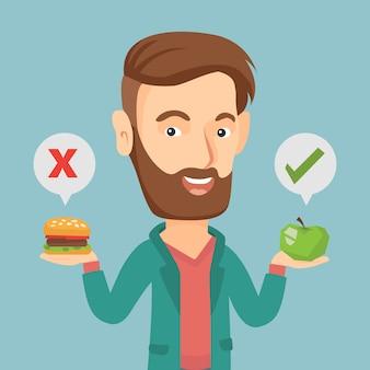 Mann, der zwischen hamburger und kleinem kuchen wählt.