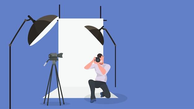 Mann fotograf, der foto mit männlichem kameracharakter macht, der auf knie steht und modernes fotostudio-interieur mit horizontaler voller länge der blitzausrüstung schießt