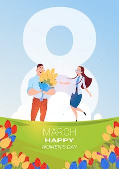 Mann-gruß-mädchen mit am 8. märz anwesendem blumenstrauß der tulpen-glücklichen internationalen frauen-tageskarte