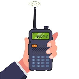 Mann hält ein walkie-talkie in der hand für die kommunikation.