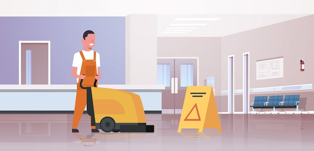 Mann hält professionelle waschmaschine männlicher reiniger hausmeister in uniform reinigung service bodenpflege moderne krankenhaus wartehalle korridor interieur