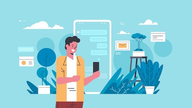 Mann hält smartphone lässig kerl mit online-mobile-chat-anwendung social media netzwerk kommunikationskonzept flaches porträt horizontal