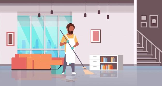Mann in handschuhen und schürze waschen boden kerl mit mopp tun hausarbeit reinigungskonzept modernes haus wohnzimmer interieur horizontal in voller länge