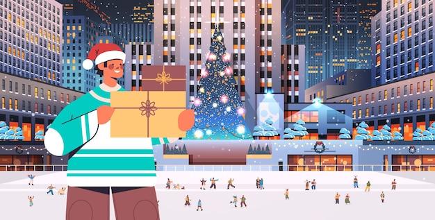 Mann in santa hut hält geschenkbox frohe weihnachten frohes neues jahr winterferien feier konzept nacht nacht stadtbild hintergrund horizontale illustration