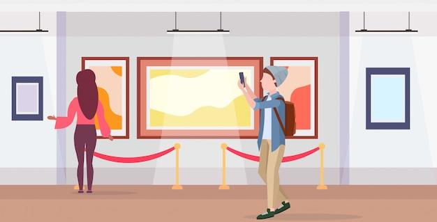 Mann kunstgalerie besucher, der selfie foto auf smartphone-kamera lässig männliche zeichentrickfigur in hut mit rucksack posiert modernen museum interieur in voller länge horizontal