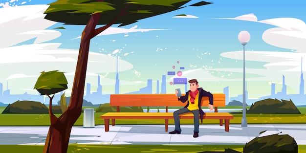 Mann mit dem smartphone, der auf bank im stadtpark sitzt