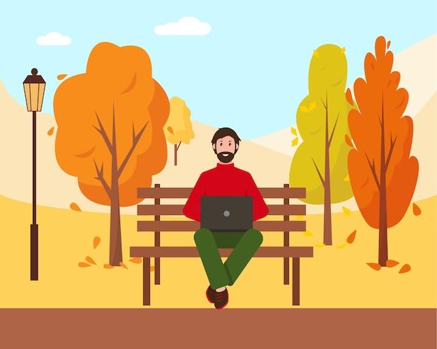 Mann mit laptop sitzt auf der bank im park.