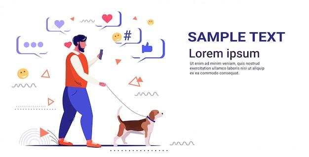 Mann mit online-mobile-app social-media-netzwerk chat-blase kommunikation digitale sucht konzept kerl zu fuß mit hund kopie raumskizze in voller länge horizontal