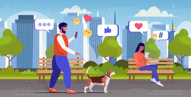 Mann mit online-mobile-app social-media-netzwerk chat-blase kommunikation digitale sucht konzept kerl zu fuß mit hund stadtbild hintergrund skizze in voller länge horizontal