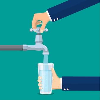 Mann öffnet einen wasserhahn mit seiner hand, die ein glas hält. küchenarmatur