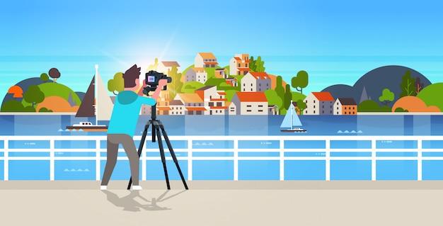 Mann-reisefotograf, der naturbild des bergstadtinsel-kerls unter verwendung der dslr-kamera auf stativlandschaftshintergrund horizontal nimmt