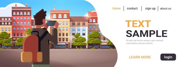 Mann reisender fotografiert stadtgebäude auf smartphone kamera kamera konzept rückblick tourist mit rucksack sightseeing architektur moderne stadt straße horizontale kopie raum porträt