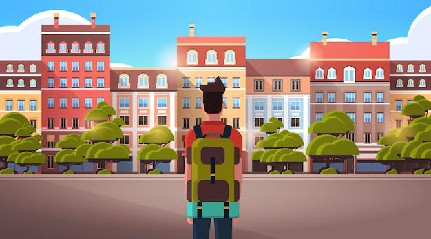 Mann reisender zu fuß im freien genießen blick auf moderne stadtgebäude sommerreise urlaub konzept rückansicht tourist mit rucksack sightseeing architektur stadtstraße horizontales porträt