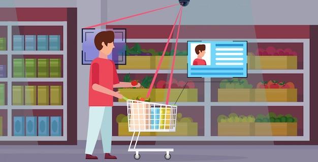 Mann schiebt einkaufswagen mit lebensmitteln identifizierung gesichtserkennung konzept überwachungskamera überwachung cctv-system lebensmittelgeschäft supermarkt innenraum in voller länge horizontal