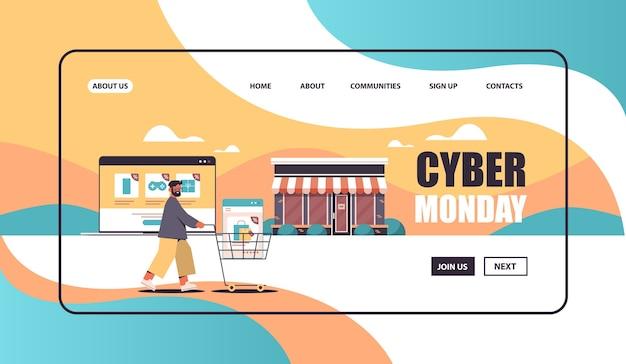 Mann schiebt online-einkäufe in trolley cart cyber montag verkauf urlaub shopping rabatte e-commerce-konzept kopie platz