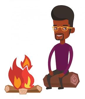 Mann sitzt auf baumstamm nahe lagerfeuer im camping.