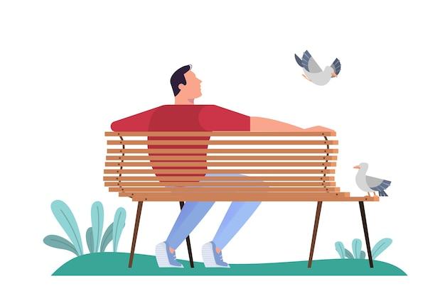 Mann sitzt auf der bank im park. erwachsener männlicher charakter