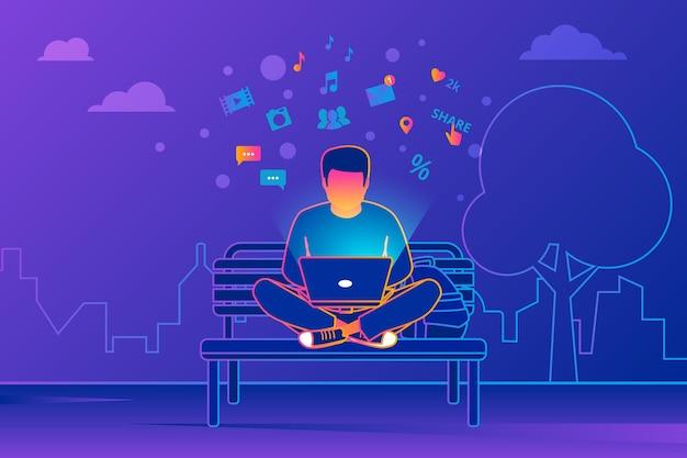 Mann sitzt im park und arbeitet mit laptop-social-media-suche nach nachrichten, e-mails und sms