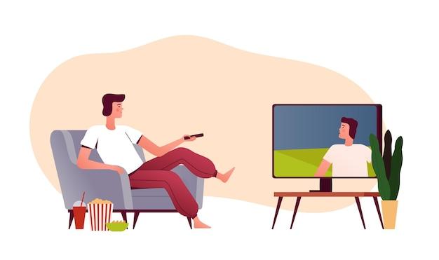 Mann sitzt in seinem haus auf einem sessel mit popcorn und sieht fern