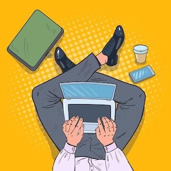 Mann sitzt mit laptop auf dem boden