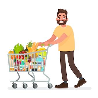 Mann trägt einen einkaufswagen voller lebensmittel im supermarkt.