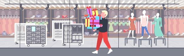 Mann trägt stapel von verpackten geschenkboxen großen saisonalen verkauf shopping-konzept kerl hält bunte geschenke moderne boutique mode shop außen in voller länge horizontal