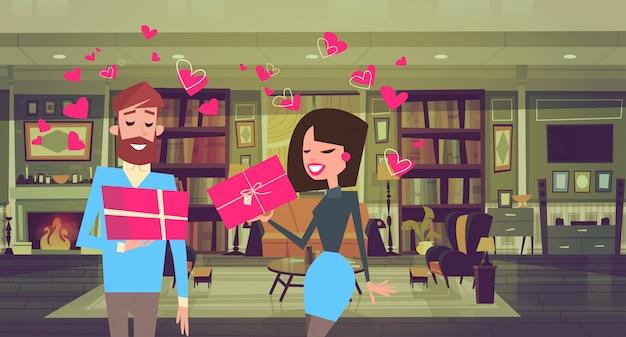 Mann und frau, die geschenkboxen über herz-form-paar mit valentinsgruß-tagesgeschenken halten