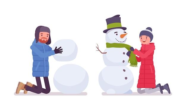 Mann und frau in einer daunenjacke machen schneemann, tragen weiche warme winterkleidung, klassische schneestiefel und hut
