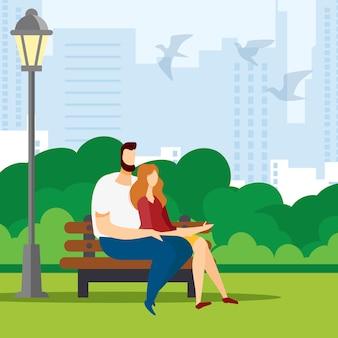 Mann und frau sitzen auf der bank im park.