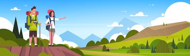 Mann-und frauen-touristen mit rucksäcken über den schönen natur-landschaftshintergrund-paaren, die horizontale fahne wandern