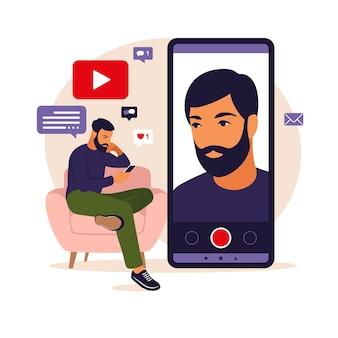 Mannvideoblogger, der auf sofa mit telefon sitzt und video mit smartphone aufzeichnet