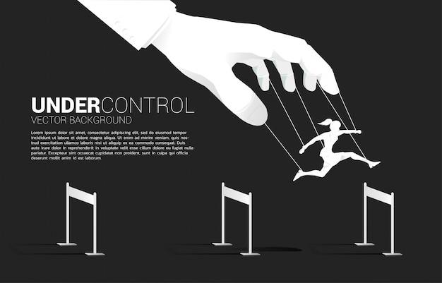 Marionettenmeister, der die silhouette der geschäftsfrau kontrolliert, läuft und springt über hürdenhindernis. konzept der manipulation und des mikromanagements