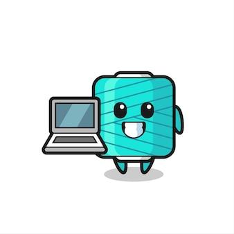 Maskottchen-illustration der garnspule mit einem laptop, süßes design für t-shirt, aufkleber, logo-element