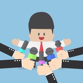 Medienmikrofone vor geschäftsmann gehalten
