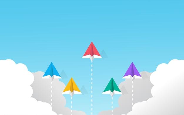Mehrfarbige papierflugzeuge, die im himmelskonzept fliegen