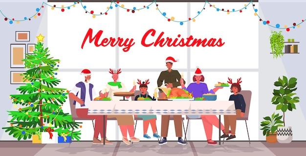 Mehrgenerationenfamilie in weihnachtsmützen, die weihnachtsessen neujahrswinterferien-feierkonzept wohnzimmerinnenraum in voller länge beschriftende grußillustration haben