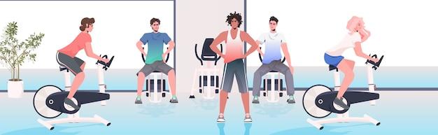 Menschen, die körperliche übungen auf trainingsgeräten fitness workout gesunden lebensstil konzept modernen fitnessraum interieur tun