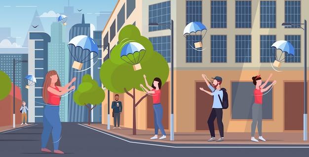 Menschen, die paketboxen fangen, die mit fallschirm vom himmeltransportversandpaket luftpost-expresszustellungskonzept herunterfallen, moderne stadtstraße stadtbildhintergrund in voller länge horizontal