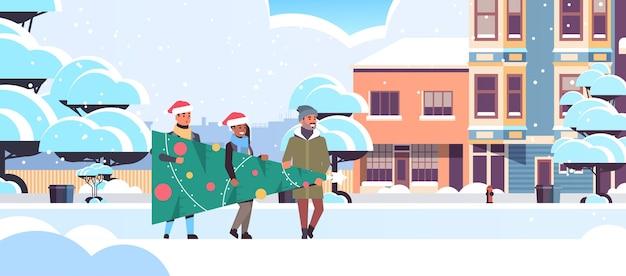 Menschen, die tannenbaum tragen, der für frohe weihnachten frohes neues jahr feiertagsfeierkonzept-mischungsrassenfreunde trägt, die weihnachtsmützen tragen, schneebedecktes stadtstraßen-stadtbild horizontales vekt in voller länge