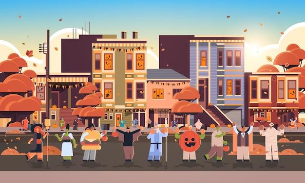 Menschen, die verschiedene monsterkostüme tragen, gehen in stadttricks und behandeln glückliches halloween-partyfeierkonzept stadtstraßengebäude außerhalb des stadtbildes