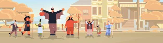 Menschen, die verschiedene monsterkostüme tragen, gehen in stadttricks und behandeln glückliches halloween-partyfeierkonzept stadtstraßengebäude stadtbild