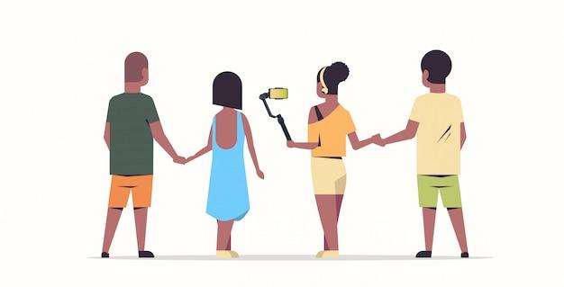 Menschen gruppe mit selfie stick männer frauen, die foto auf smartphone-kamera freunde haben spaß männlich weiblich rückansicht cartoon-zeichen in voller länge flachen weißen hintergrund horizontal