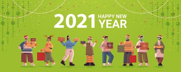 Menschen in weihnachtsmützen, die geschenke halten, mischen rassenmännerfrauen, die 2021 neujahr und weihnachtsferien horizontale vektorillustration in voller länge feiern