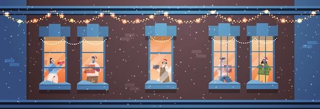 Menschen in weihnachtsmützen, die geschenke halten, mischen rassennachbarn, die in fensterrahmen stehen neujahrs-weihnachtsfeiertagsfeier selbstisolationskonzept, das hausfassade horizontale vektorillustration baut
