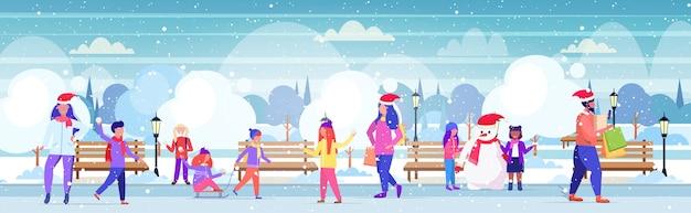 Menschen in weihnachtsmützen gehen im freien männer frauen halten einkaufstaschen kinder, die spaß weihnachten einkaufen winterferien konzept städtischen schneebedeckten park landschaft haben Premium Vektoren