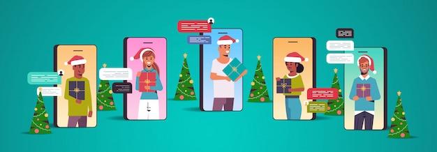 Menschen in weihnachtsmützen mit chat-app social network chat-blase kommunikationskonzept